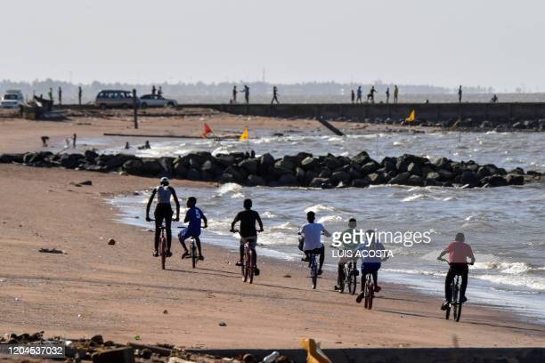 Boys ride their bikes on the beach in Georgetown Guyana on March 1 2020 Guyana goes to the polls March 2 in a pivotal election in one of South...