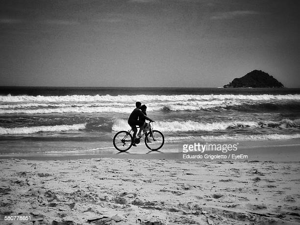 Boys Riding Bicycle At Beach