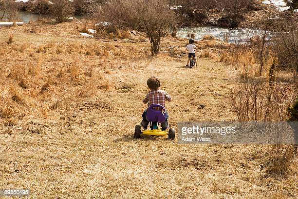 Boys riding bikes down hill towards stream.