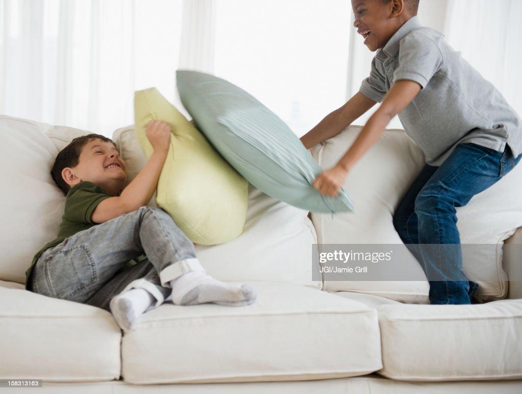 Boys rough housing on sofa : Stock Photo