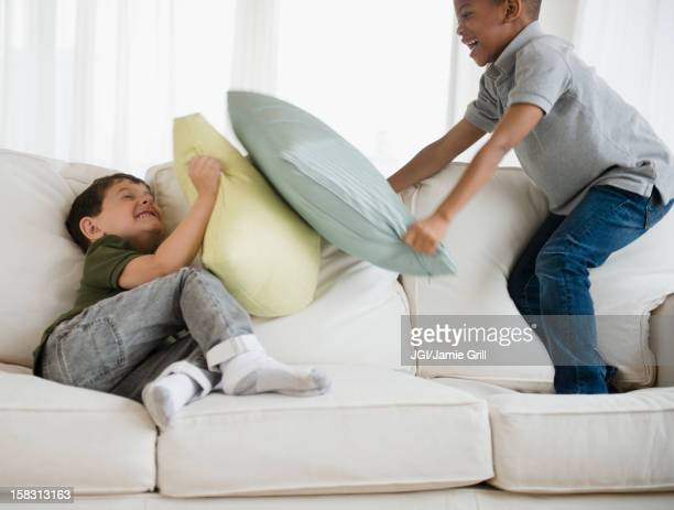Boys rough housing on sofa