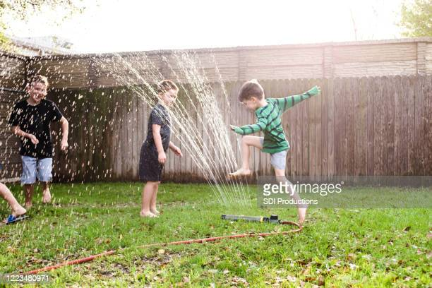boys run and jump over sprinkler on hot summer day - hose stock pictures, royalty-free photos & images