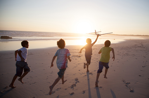 Boys running along beach with a toy plane - gettyimageskorea