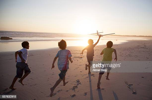 boys running along beach with a toy plane - kindertijd stockfoto's en -beelden