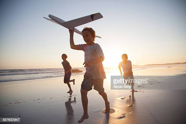 boys running along beach with a toy plane - imagination stock pictures, royalty-free photos & images
