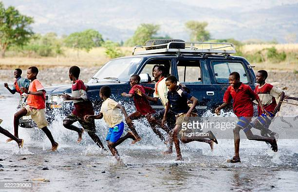 Boys running alongside 4x4 vehicle in Ethiopia