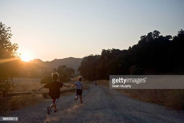 boys running down gravel road - calabasas stock photos and pictures