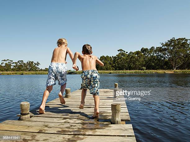 2 boys running on a jetty