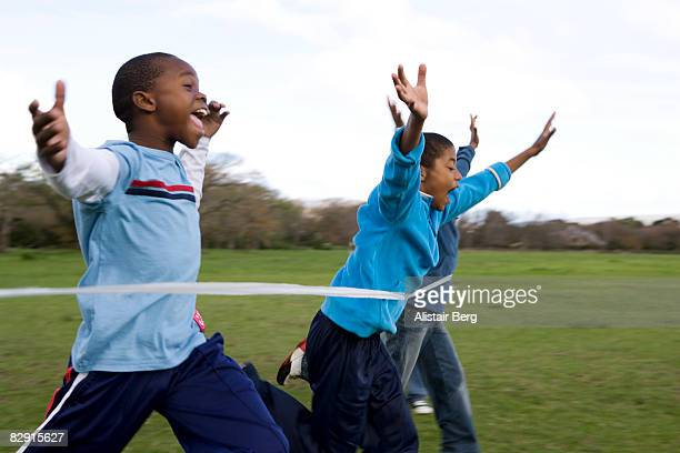 boys running through finishing line - rushing the field stock pictures, royalty-free photos & images