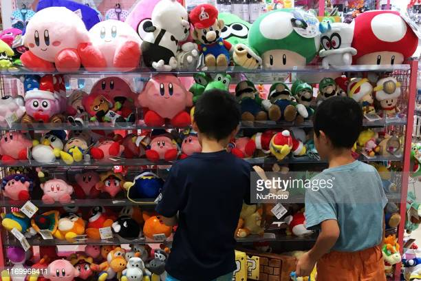 Boys seated front a Super Mario figure watch at its showroom in Tokyo September 21 2019
