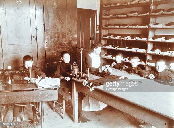Boys sewing at the Boys Home Industrial School Regent's Park Road London 1900 Young boys sew by hand and use sewing machines The one on the left is a...