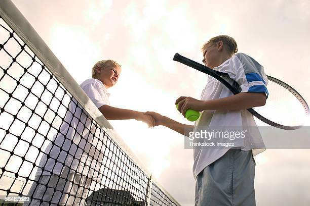 Boys shaking hands after tennis game