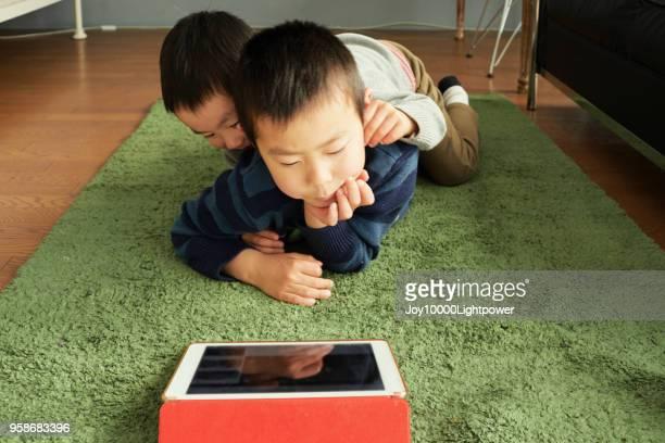 デジタル タブレットで家庭で社会的なメディアを示す男の子 - 兄弟 ストックフォトと画像