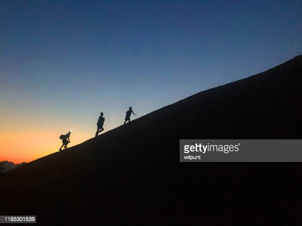 jungen silhouette skalieren einen steilen hügel bei sonnenuntergang - felsspitze stock-fotos und bilder