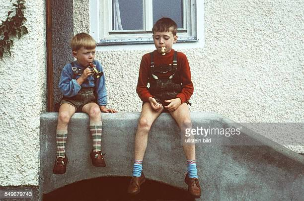 Boys sit on a balustrade in front of a house 1950s