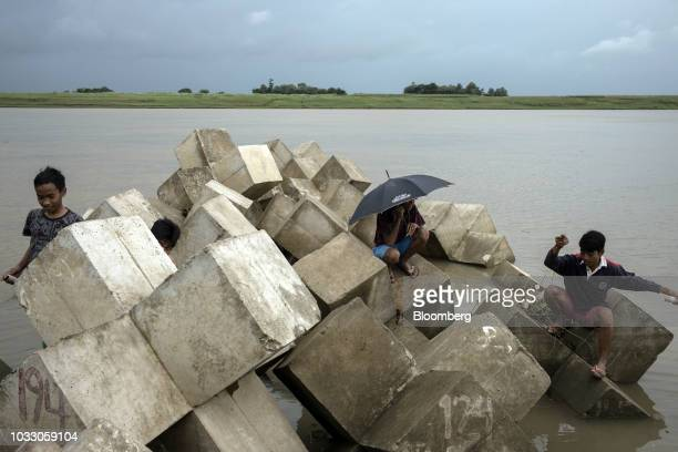 Boys sit on a breakwater while fishing along the Cagayan River ahead of Typhoon Mangkhut's arrival in Tuguegarao Cagayan province the Philippines on...