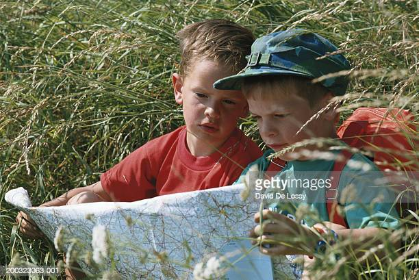 Boys (4-7) sitting in field reading map