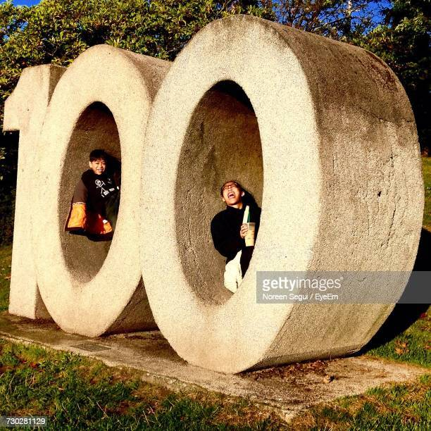 Boys Sitting In Number 100 Shaped Concrete Structure At Park