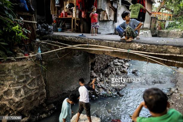 Boys sitting on a makeshift raft play in a river during a monthlong break from school in a slum area of Jakarta Indonesia on June 24 2019