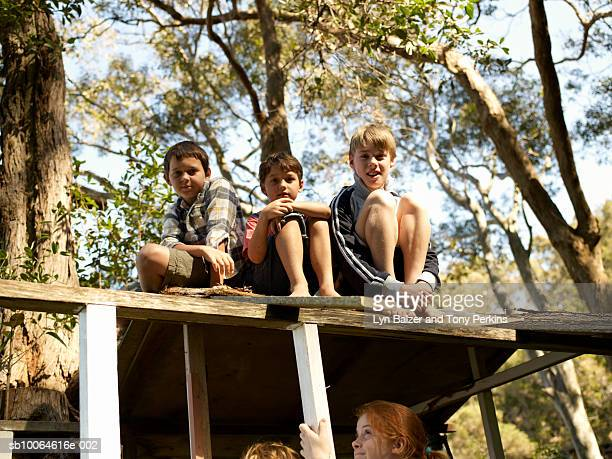 Boys (7-11) sitting on roof of cubby house, low angle view