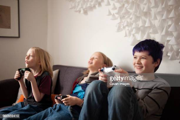 Boys sitting on sofa and playing video game