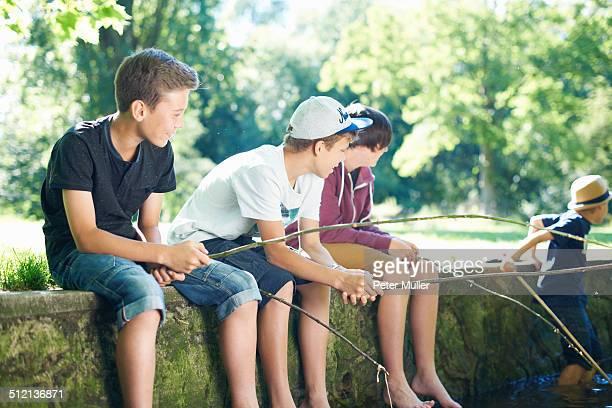 Boys sitting on wall, fishing