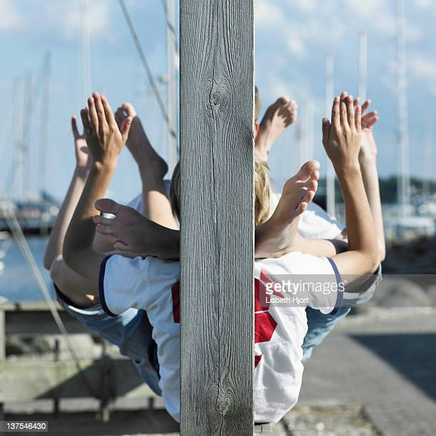 boys sitting together on pier - teen boy barefoot stock photos and pictures