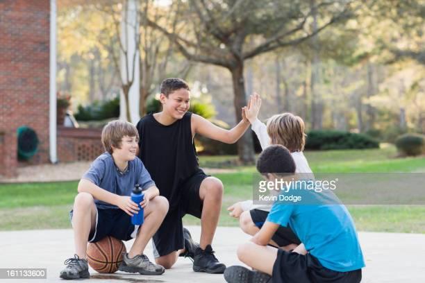 Boys sitting with basketball