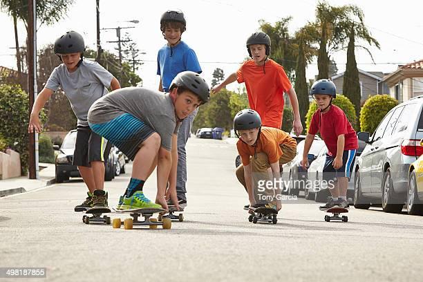 Boys skateboarding on road