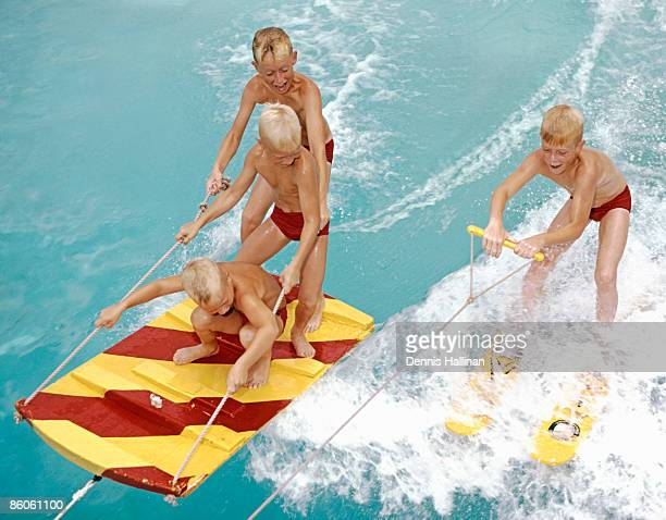 Boys skiing and water sledding