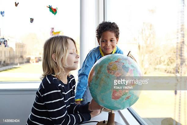 2 boys smiling,  looking at globe