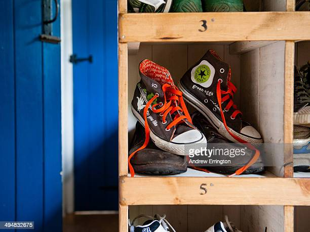 Boy's sneakers over adult outdoor shoes in numbered locker