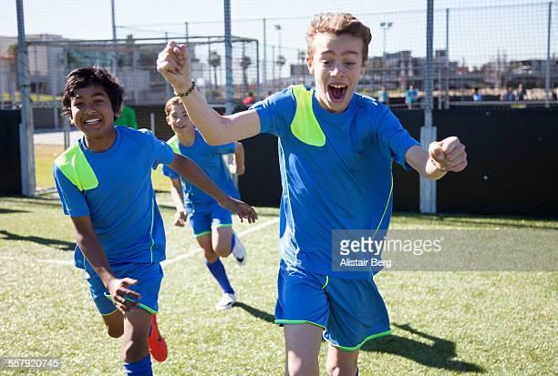 Boys soccer team celebrate scoring a goal