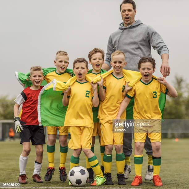 a boys soccer team celebrating a victory with their male coach posing for a group photo - football team stock pictures, royalty-free photos & images