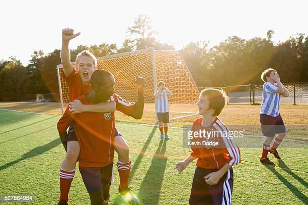 boys' soccer team (8-9) celebrating victory - spiel sport stock-fotos und bilder