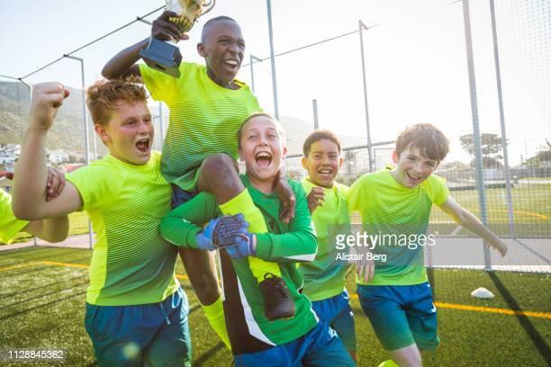 boys soccer team celebrating with trophy - fußballmannschaft stock-fotos und bilder