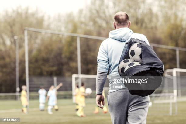 a boys soccer team during a football training session with a handsome bearded redhead male coach - coach stock pictures, royalty-free photos & images