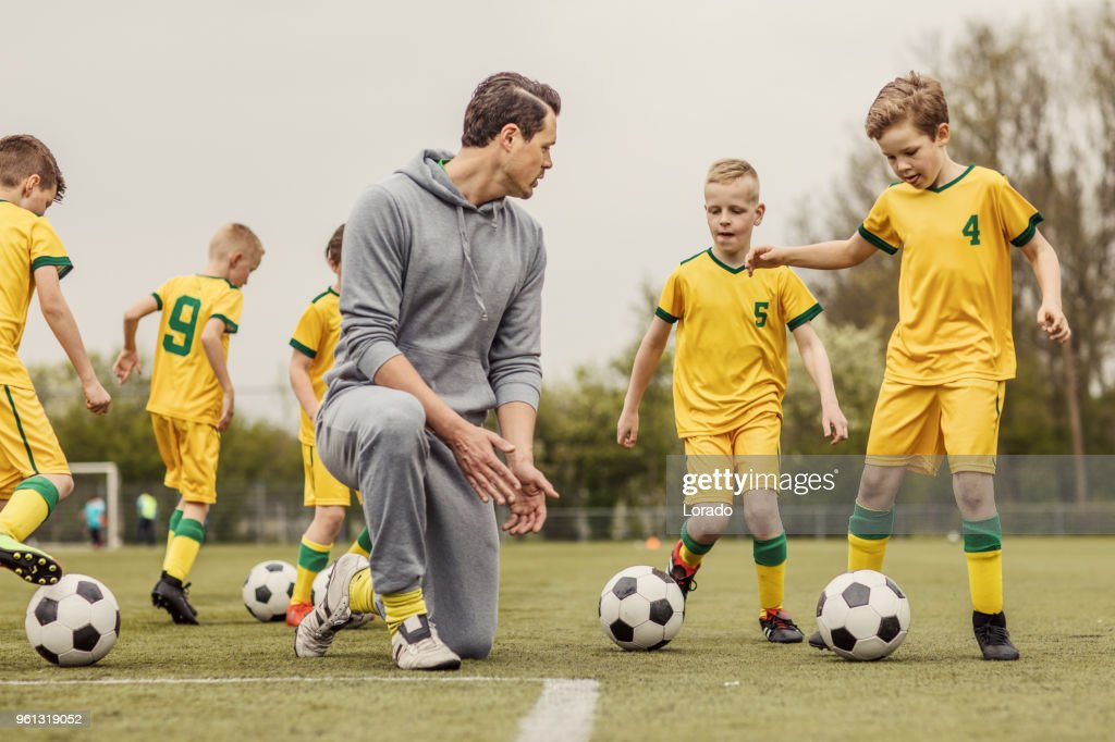 Un equipo de fútbol de los muchachos durante una sesión de entrenamiento intensa de fútbol con un entrenador masculino guapo : Foto de stock