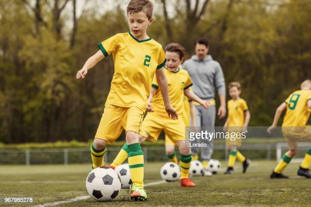 ein jungen-fußball-team während einer intensiven fußballtraining mit einem schönen männlichen trainer - trainingsdrill stock-fotos und bilder