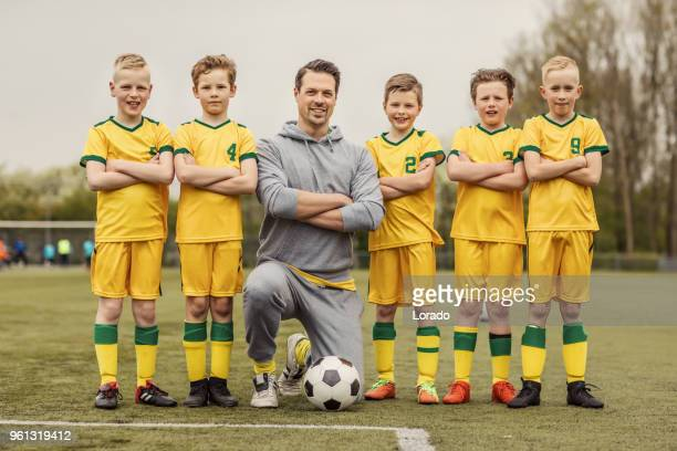 a boys soccer team posing for a team photo during a football training session with a handsome male coach - football team stock pictures, royalty-free photos & images
