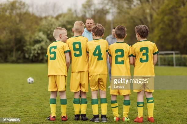 een jongens voetbal team de oprichting van een defensieve muur tijdens een voetbalwedstrijd - verdediger voetballer stockfoto's en -beelden