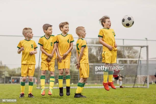 en pojkar fotboll team inställning upp en försvarsmur under en fotbollsmatch - lagsport bildbanksfoton och bilder