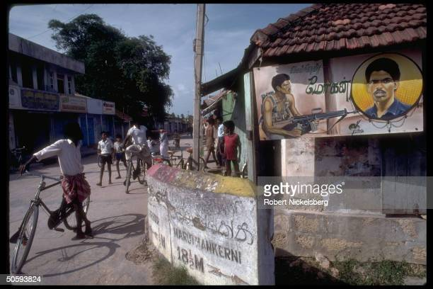 Boys socializing on street by secessionist LTTE Tamil Tiger guerrilla billbd in strife torn Jaffna peninsula