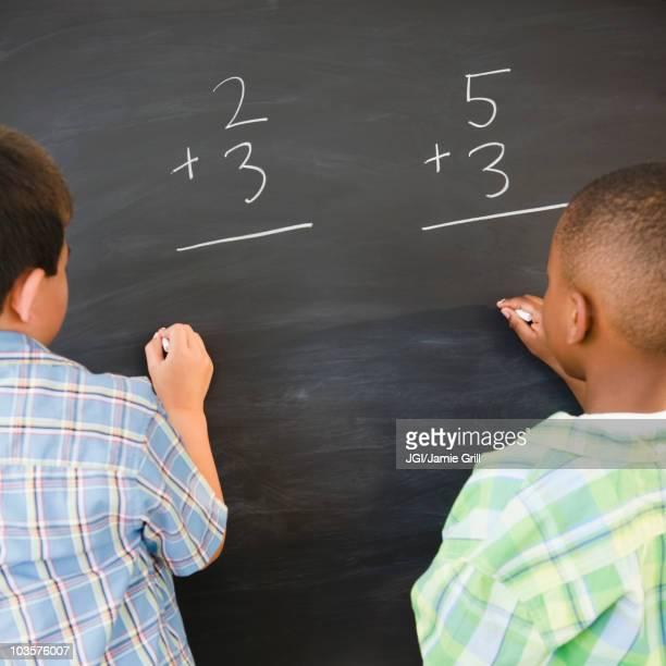 Boys solving math problems on blackboard