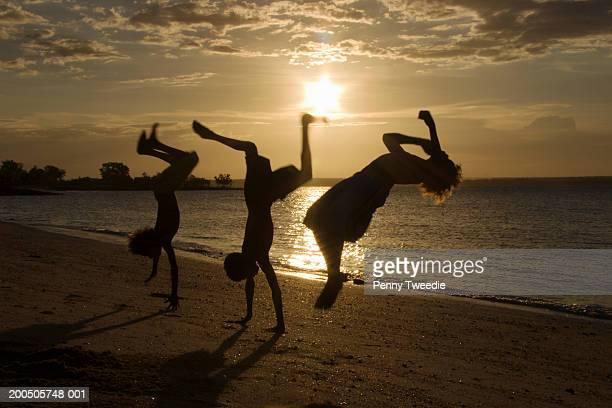 boys somersaulting on beach at sunset, silhouette - アーネム ストックフォトと画像