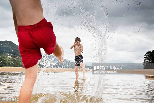 Boys splashing in shallow pool at beach