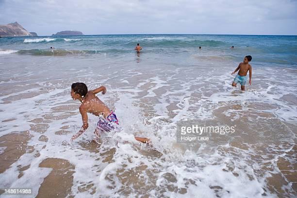 Boys splashing in waves of Porto Santo beach.