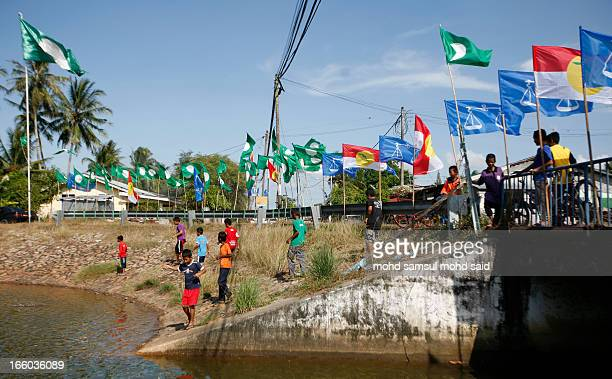 Boys stand at a roadside railing, under flags of Malaysia parties politics, near a bridge in Tumpat April 3, 2013. Malaysian Prime Minister Najib...