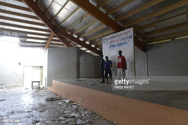 Boys stand in a damaged building on March 19 2015 in the Catholic french speaking Lycee De Montmartre 5 km from Port Vila after Severe Tropical...
