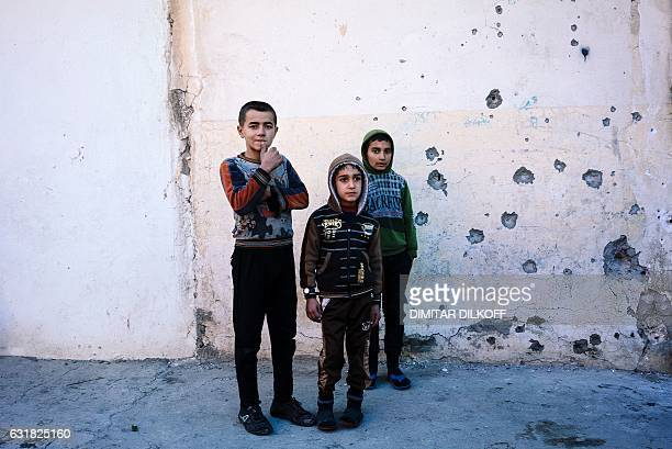 Boys stand watching as demining experts from the Iraqi army search for boobytrapped buildings in eastern Mosul on January 16 during an ongoing...